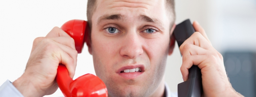 Man holding two phones with a disgusted look on his face